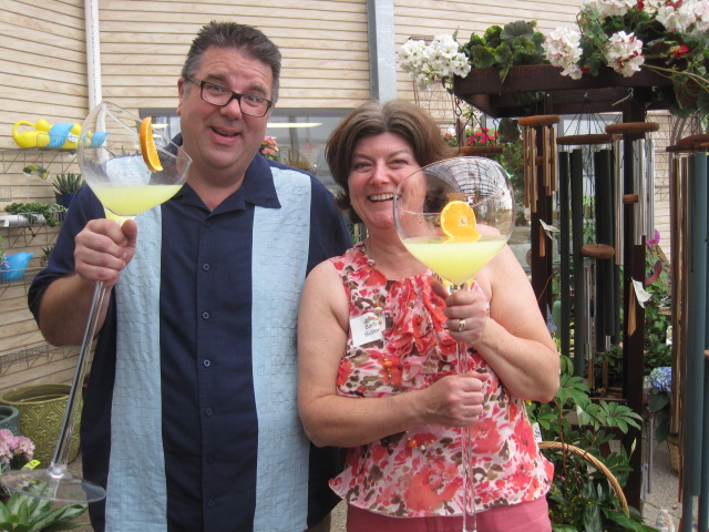 Waukesha Floral's Marty Loppnow toasts with Interfaith Senior Program's Barb Butler during a scorching hot Festival of Flowers (over 90 degrees in the greenhouse!)